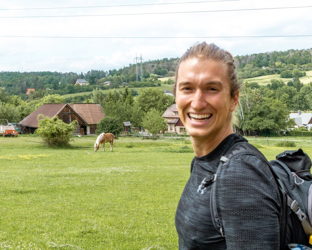 Dom hiking in the Czech Republic with a horse in the background.